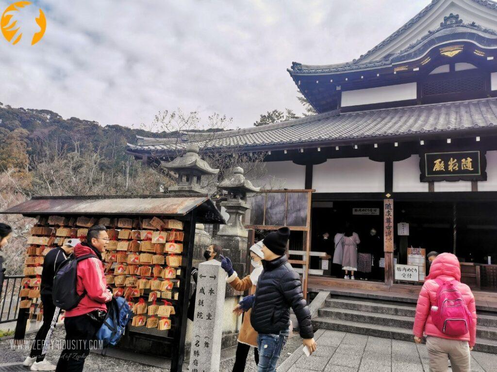 Tourist writing Love wishes inside Jishu Shrine at Kiyomizu-dera