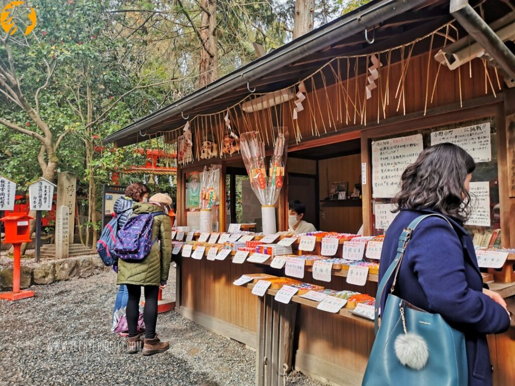 tourist buying charms and ema inside the Nonomiya Shrine at Arashiyama